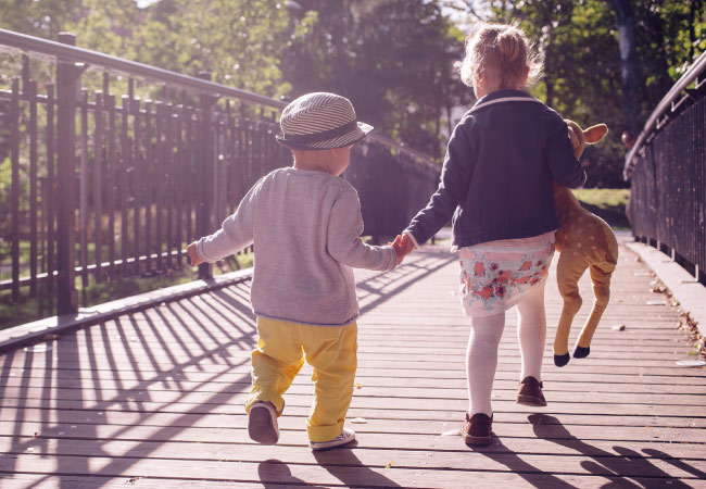 brother and sister walking on a bridge
