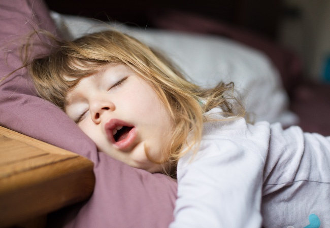 girl sleeping in bed before going to the pediatric dental office