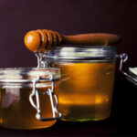 Closeup image of 2 jars of honey with a wooden stir stick