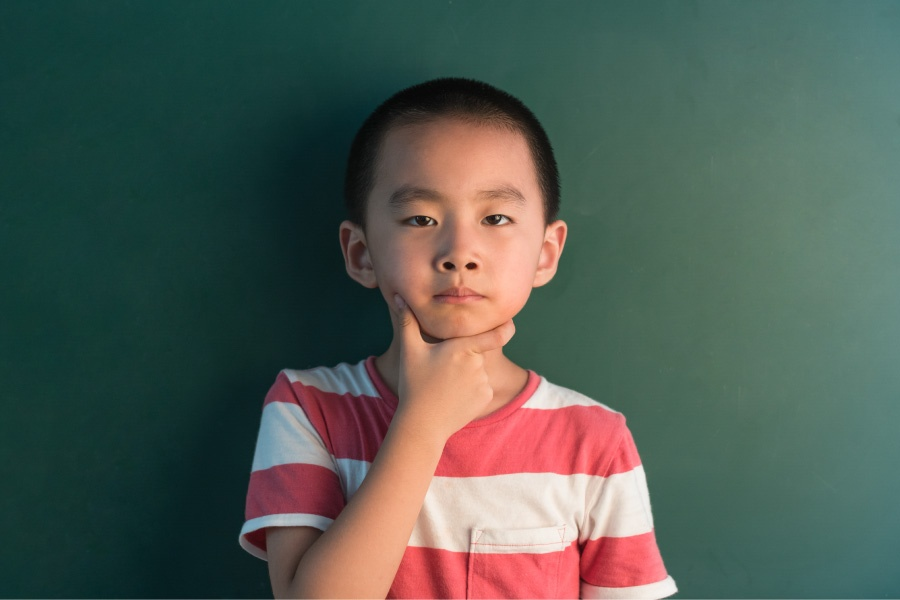Boy in red and white striped shirt wonders if tooth decay is reversible while standing against a green wall