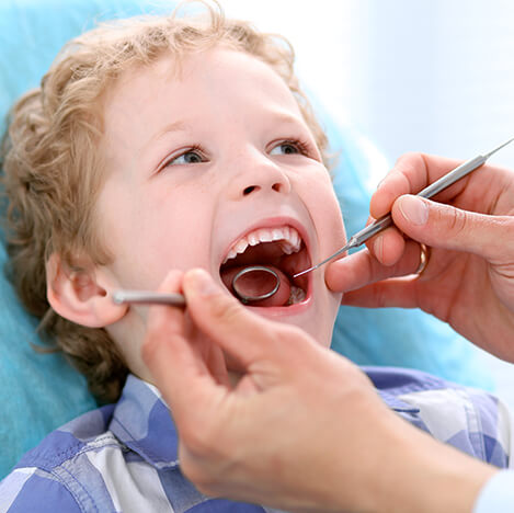 young boy having his teeth examined
