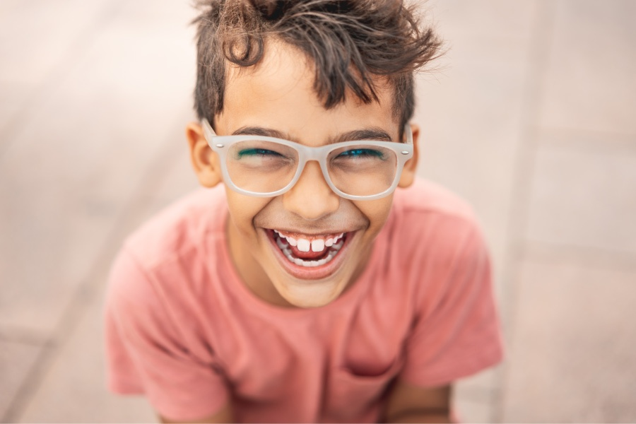 Brunette boy with glasses smiles after getting dental sealants to prevent tooth decay and cavities
