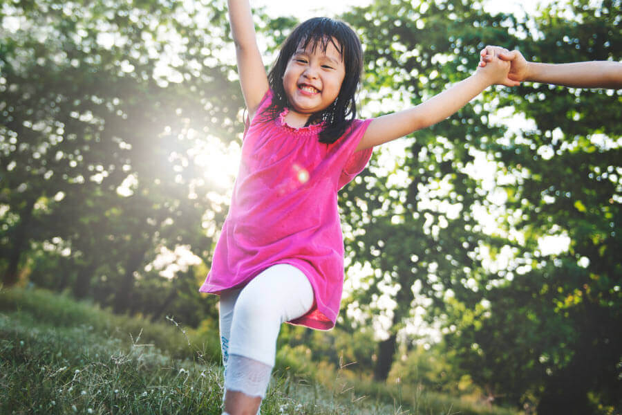 Little girl with healthy baby teeth in a pink dress smiles while playing outside