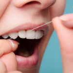 Closeup of a woman's mouth as she is flossing with string floss