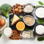 Aerial view of calcium rich foods, such as spinach, broccoli, beans, nuts, milk, yogurt, canned fish, eggs, and cheese